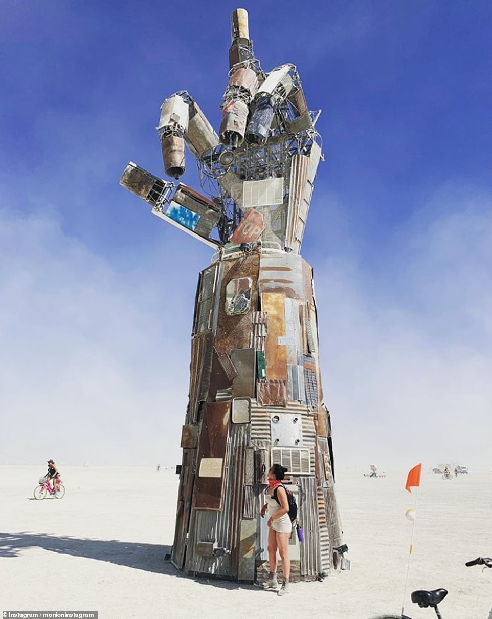 A festival goer is standing next to a cheeky sculpture giving Black Rock City, and Burning Man, a metal constructed middle finger